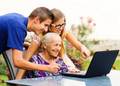 elderly woman and her grandchildren looking on the laptop