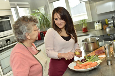 caregiver preparing meal with elderly woman