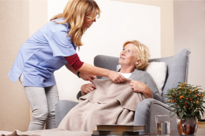 caregiver assiting on blanket to elderly woman
