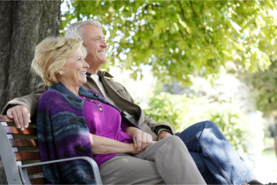 elderly couple sitting in the bench outside