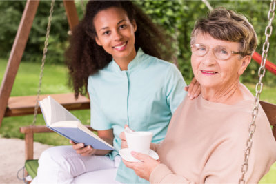 caregiver reading a book with elderly woman